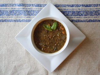 Lentil soup in a white bowl on a kitchen towel background