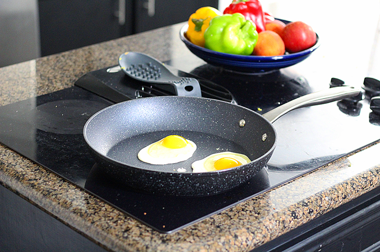 The non-stick Bialetti Titan Fry Pan on a countertop stove, cooking eggs with fresh produce on the counter beside it.