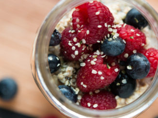 Cardamom Overnight Oats in glass jar on countertop with raspberries and blueberries