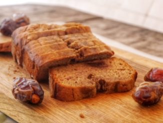 Carob Date Bread on a cutting board with fresh dates