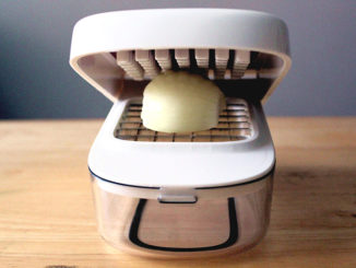 OXO Good Grips Vegetable Chopper with Easy-Pour Opening with an onion prepared for chopping