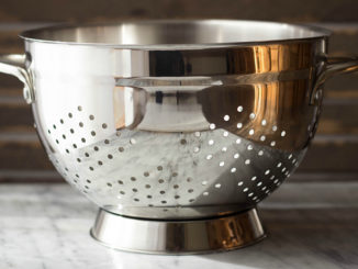 Empty stainless steel colander on marble countertop