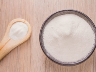 A scoop of powder next to a bowl of collagen powder