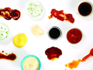Different condiments on white background