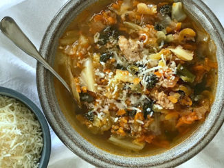 Easy Sausage, Cabbage, Kale and Carrot Soup in a bowl with grated parmesan cheese for garnish