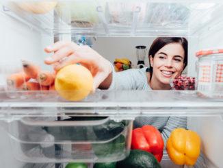 Women reaching into back of fridge to grab lemon
