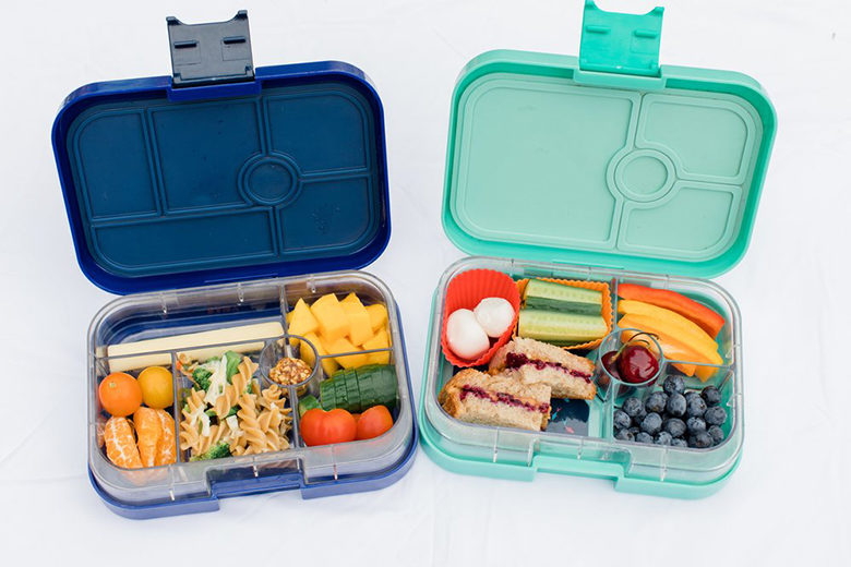 two lunch bento boxes filled with healthy fruits, veggies and more
