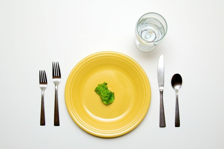A place setting with a single piece of lettuce on the plate.