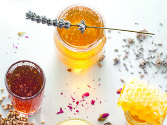 Honey variety with bee's comb in a glass jars with flowers and fresh herbs.