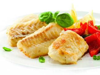 Fish filet served with vegetables on white plate