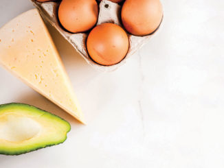 A platter with an avocado, cheese and eggs.
