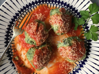 Spinach and Ricotta Malfatti, covered in tomato sauce and grated Parmesan cheese, shot from above. This meal is on a black and white patterned plate and garnished with a sprig of herb