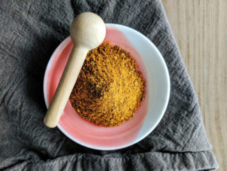 African spice blend Ras el Hanout in a bowl on a gray kitchen towel
