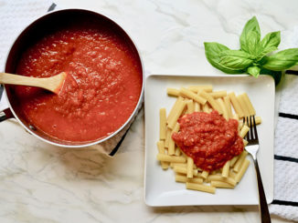 Lagostina Rossella Red Ceramic and Stainless Steel 1.6 Qt. Covered Saucepan with tomato sauce, wooden spoon next to a plate of pasta on a white marble countertop with fresh basil leaves nearby