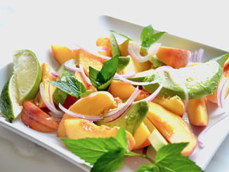 Summer Peach & Avocado Salad with Red Onion and Lime on a square white plate on a white background