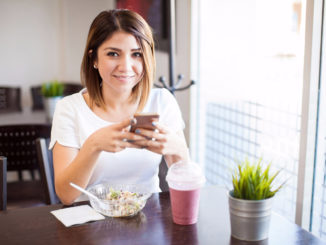 Woman using smartphone while eating salad and smoothie at cafe