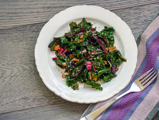 Garlicky Swiss Chard with Sesame Seaweed Sprinkle, on white plate on wooden background with napkin