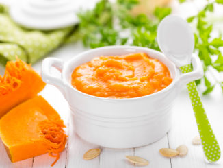 Bowl of baby food with pumpkin and herbs on white table