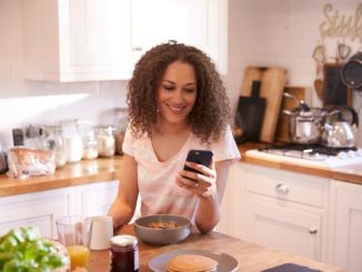 A woman in her kitchen using her phone; smiling