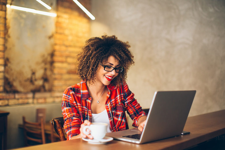 Young woman siting at cafe drinking coffee and working on laptop