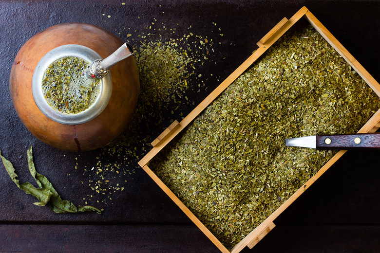Yerba mate in calabash and wooden box of dry herb.