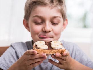 Happy boy eating delicious sandwich