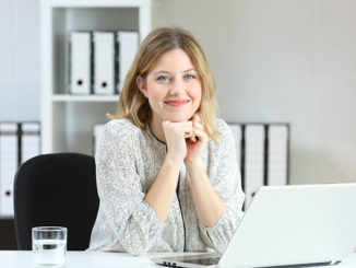 Businesswoman posing looking at you at office