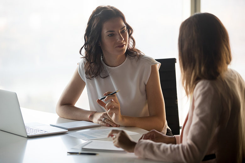 Two businesswomen discussing business project working together in office, serious female advisor and client talking at meeting, focused executive colleagues brainstorm sharing ideas
