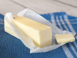 Stick of unwrapped butter on blue cloth