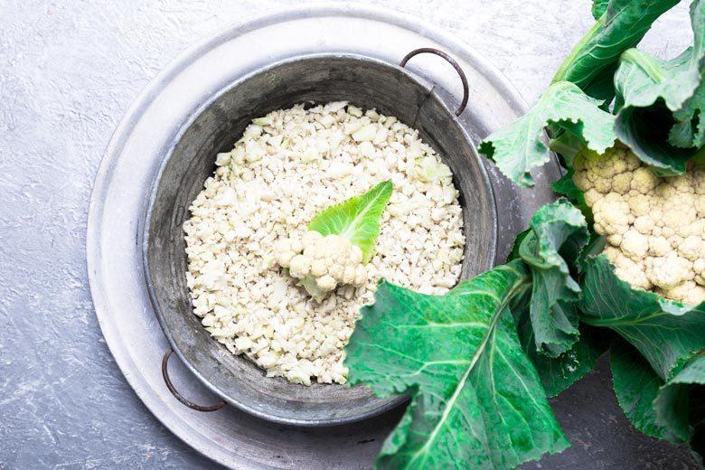 "Cauliflower ""rice"" in a metal pan with fresh greens around it"