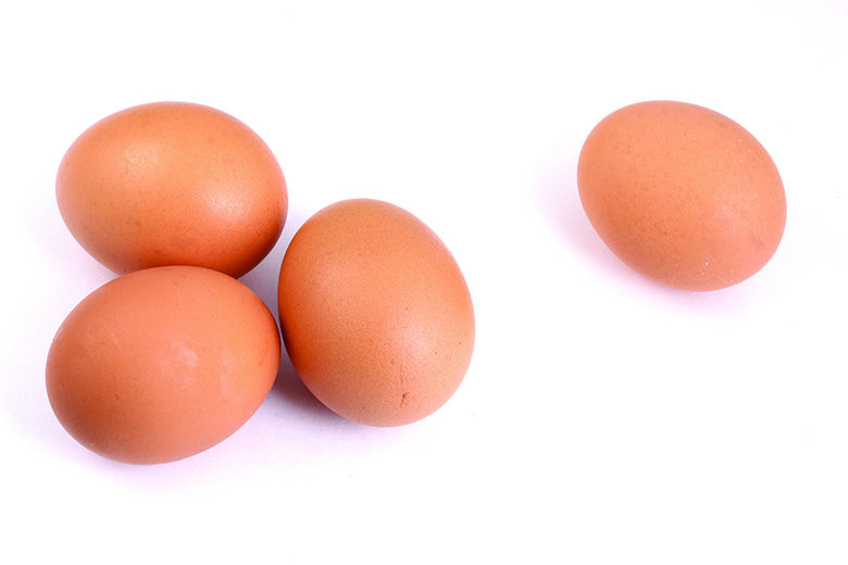Four eggs in shell on white background