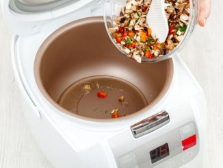 cooking fried vegetables and mushrooms in multicooker closeup