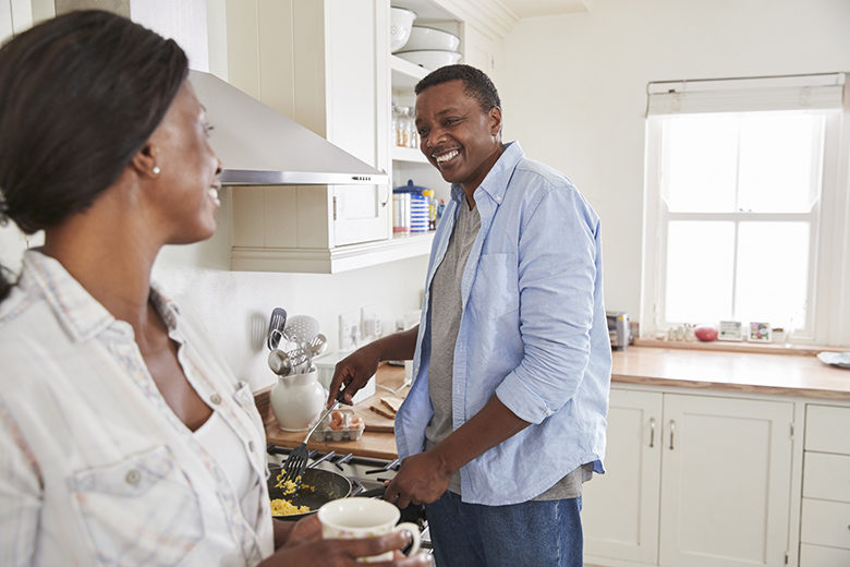 Mature Couple Chat In Kitchen As Husband Prepares Breakfast
