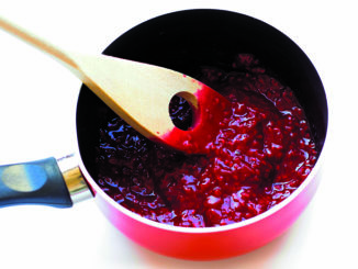 View of homemade raspberry jam in a saucepan.