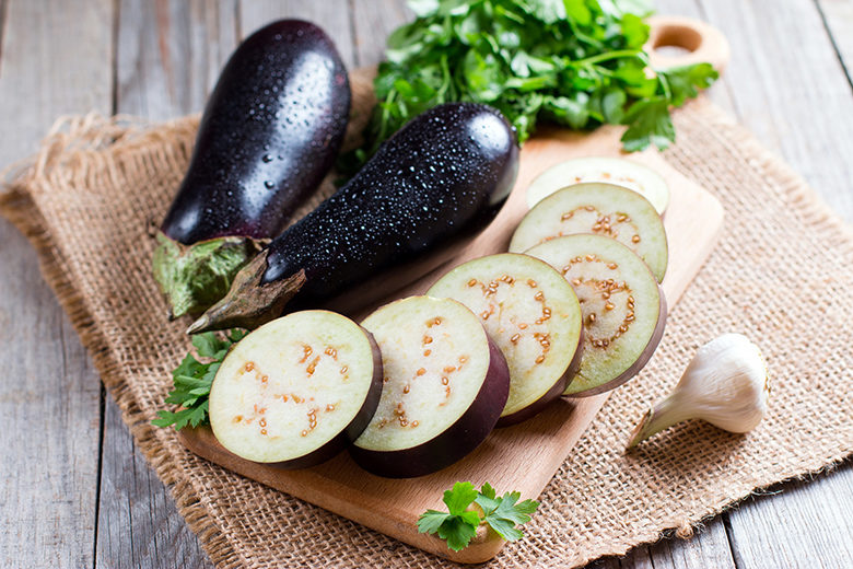 Eggplant slices on cutting board on wooden background