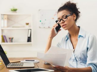 Young African American woman looks at papers while sitting at her laptop, working