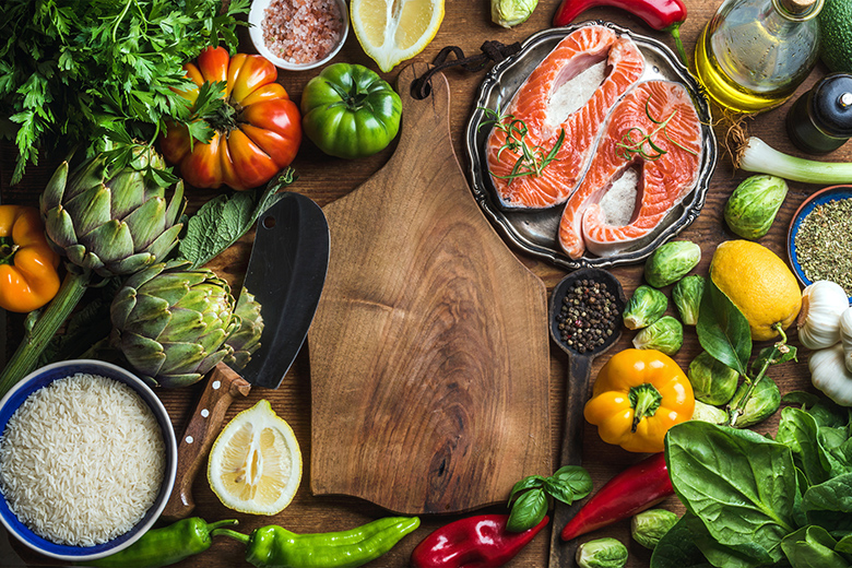 Dinner cooking ingredints. Raw uncooked salmon fish with vegetables, rice, herbs and spices over rustic wooden background