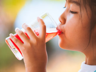Little child girl drinking red juice water with ice from glass