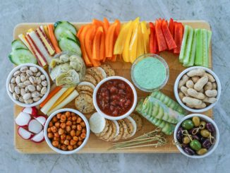 An assortment of healthy snacking options: fresh cut vegetables, nuts, whole grain crackers, etc.
