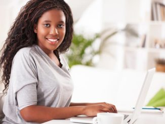 Smiling African-American woman sits at a desk, working on a laptop. She's making eye contact with the camera.