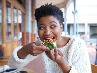 An African American woman sits outside and takes a bite of her meal
