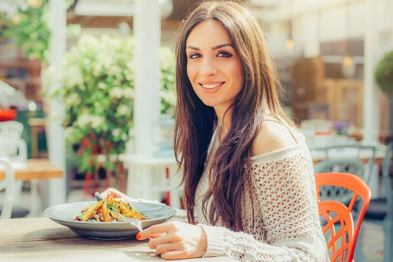 Woman eating salad while sitting at table outdoors