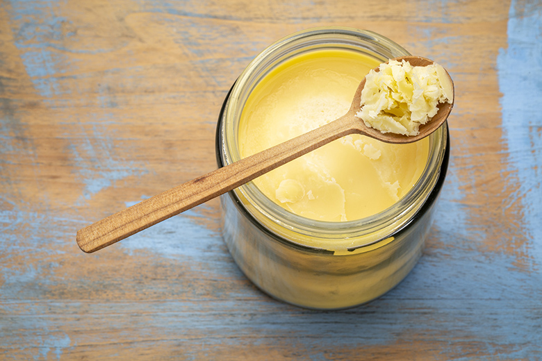 jar and spoon of ghee (clarified butter) on grunge wood - top view