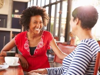 Two women meeting over coffee and laughing