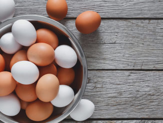 Fresh brown eggs in bowl on wood background