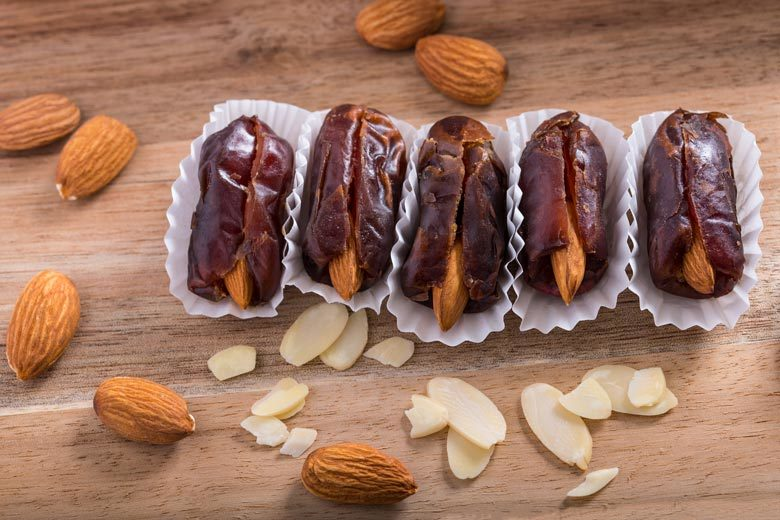 Dates stuffed with almonds lined up on wooden background with almonds scattered around
