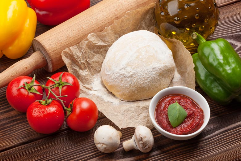 A ball of uncooked pizza dough surrounded by veggies, tomato sauce and a rolling pin