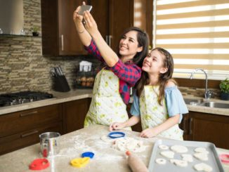 Mom and daughter in kitchen taking selfie and baking