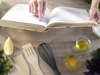 Woman reading pizza recipe in culinary book at home