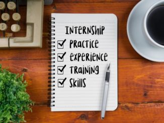 "Notebook with pen on wooden desk background; notebook has title, ""Internship,"" with checklist underneath with following items: practice, experience, training skills"